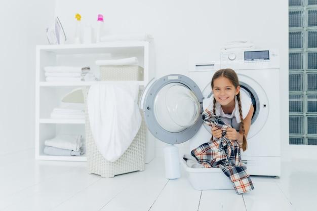 おさげの肯定的な子供は洗濯機から頭を突き出します
