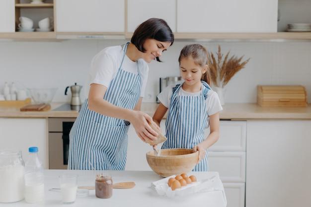 Дочь и мама любят готовить, одетые в полосатые фартуки, готовить вкусные обеды, использовать разные ингредиенты, готовить на кухне, стоять дома.