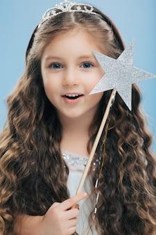 愛らしい青い目をした小さなヨーロッパの女性の王女は、長いウェーブのかかった髪、冠をかぶって、星の魔法の杖を保持しています