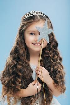 青い目で満足している美しい巻き毛の女性、魔法の杖で顔を覆っています