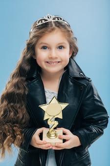 肯定的な笑顔の子供、青い目、長く鮮明な髪、星の形で報酬を保持