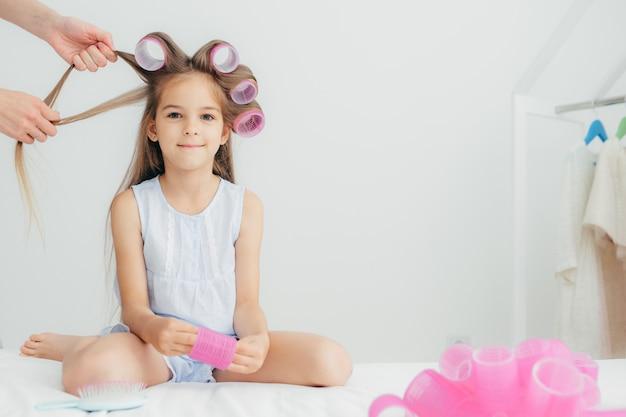 女児の頭にカーラーがあり、素晴らしい髪型になります