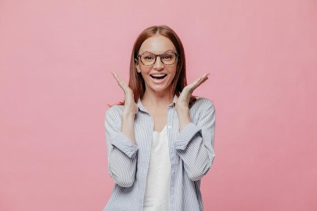 Студия выстрел радостная взволнованная женщина, одетая в полосатой рубашке, разводит руками возле лица