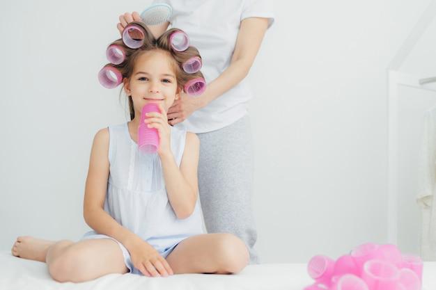 頭にカーラーをつけて喜んでいる小さな子供と母親が櫛の髪の後ろに立ってカーラーを巻く