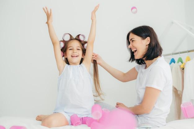陽気なブルネットの女性は、喜んで表情を持ち、手を上げ、頭にカーラーを持っている娘の髪をします