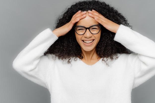 Внутренний снимок радостной оптимистичной темнокожей леди касается лба, имеет вьющиеся волосы афро