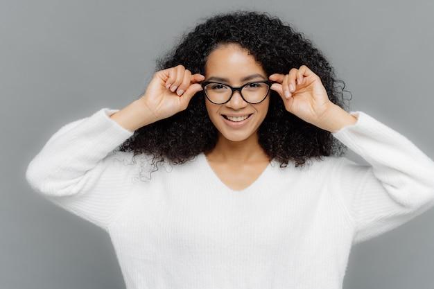 楽観的な巻き毛の女性が喜んで表情を浮かべて、眼鏡の縁に手を添える
