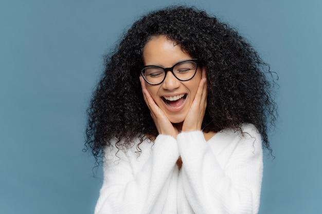 感情に訴える女性は頬に触れて喜びから笑い、目を閉じたまま、笑いを止めることはできない