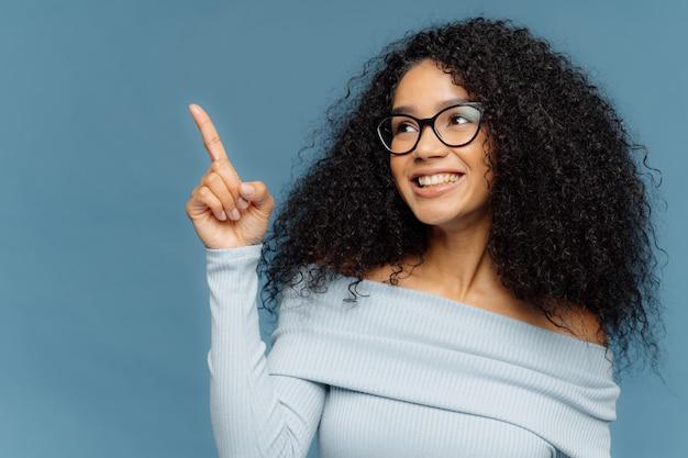 アフロの髪型で人差し指を上向きに笑顔の黒い肌の女性を満足