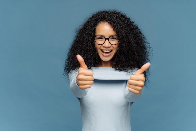 ふさふさしたアフロの髪の幸せな素敵な女性は親指をあきらめ、素晴らしいアイデアを承認します