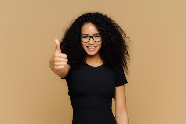 Талия вверх выстрел удовлетворенной поддерживающей женщины показывает большой палец вверх, ура лучший друг