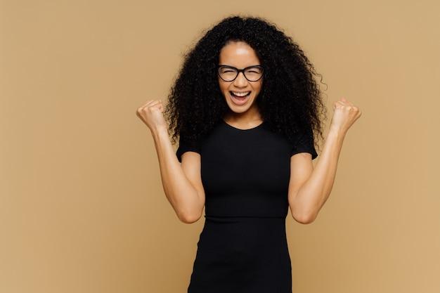 Студия выстрел из веселой аплодисменты женщина с вьющимися волосами, поднимает сжатые кулаки