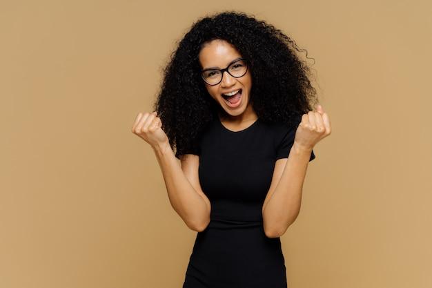 Торжествующая милая темнокожая женщина поднимает сжатые кулаки, кричит от радости