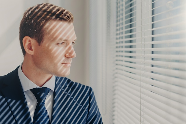 Молодой предприниматель в богатом костюме думает о будущем своей компании
