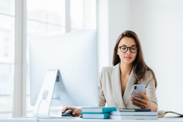 Красивая молодая женщина в элегантной одежде проверяет ленту новостей через смартфон