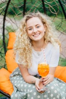 Вертикальный снимок красивой молодой блондинки с вьющимися волосами, позитивной улыбкой, проводит свободное время с друзьями, устраивает вечеринки вместе, позирует в подвесном кресле, пьет свежий летний коктейль.
