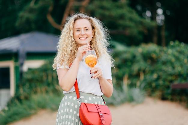Радостная европейка с кудрявыми светлыми волосами, носит повседневную одежду, держит красную стильную сумку, пьет свежий летний коктейль, гуляет по парку, радостно смотрит на дистанционные стенды на улице. концепция досуга