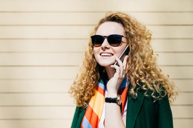 携帯電話で話している金髪の巻き毛を持つサングラスの若い笑顔のオフィスワーカー