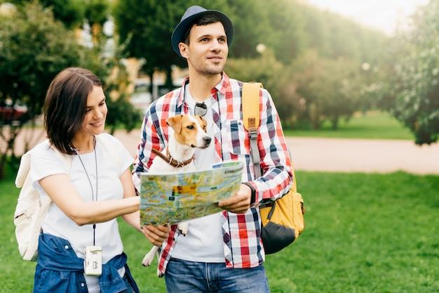 若い観光客のカップルが彼らの犬と一緒に都市を旅し、次に行く先を探している間に地図を手に持っています。彼女の夫の方向を示す都市ガイドを指して陽気な女性