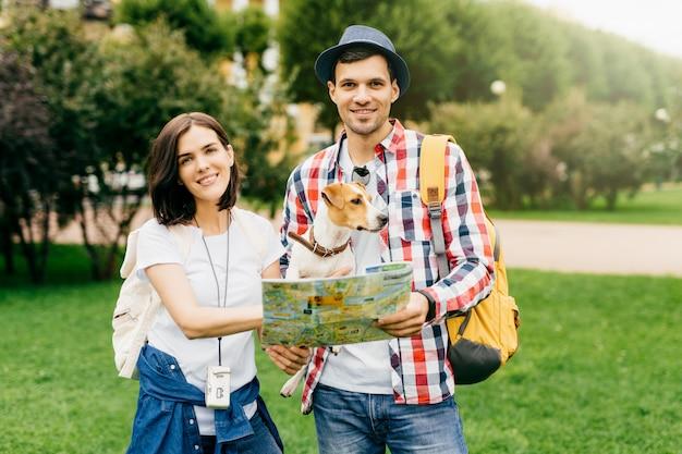 彼女の夫と犬の近くに立って、未知の都市を歩いて一緒に持って、さまざまな興味のある場所を探しながら地図を見て幸せな女。屋外に立っている若い旅行者のカップル