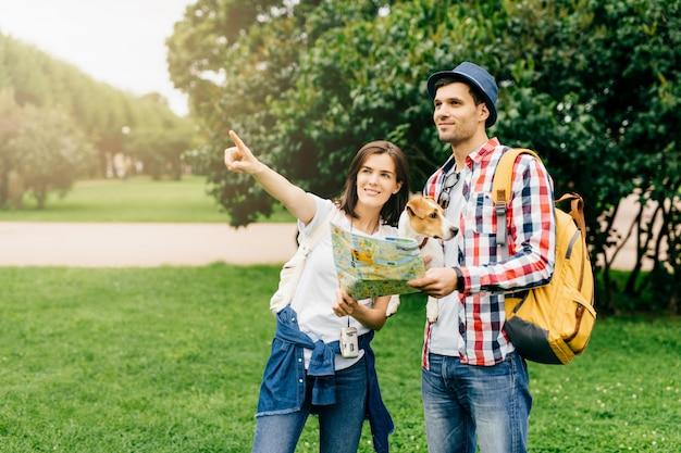 帽子と市松模様のシャツを着て彼の犬と若い男の旅行者、都市で失われた、方向に彼女の人差し指で示しているし、地図に行く場所を示す通行人の道を求めて