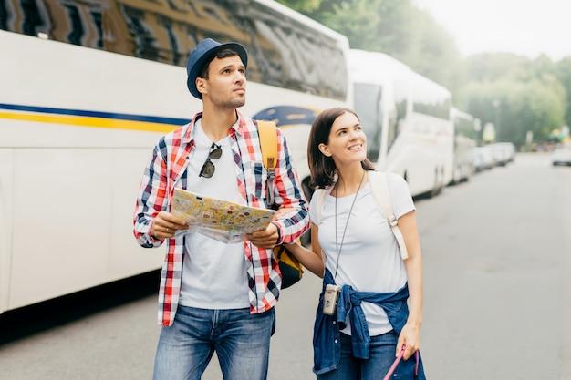 Туристы женского и мужского пола гуляют возле автобусов, держат в руках карту, ищут гостиницу, где остановиться. энергичные путешественники ищут место в неизвестном месте. люди, концепция исследования