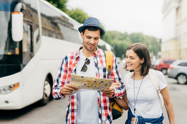 帽子とシャツを着た陽気な男、市内地図を保持し、笑顔で見て、彼の女性の友人の近くに立って、街を歩いて、新しいエンターテイメントを探索します。シティガイドと男性と女性の観光客。
