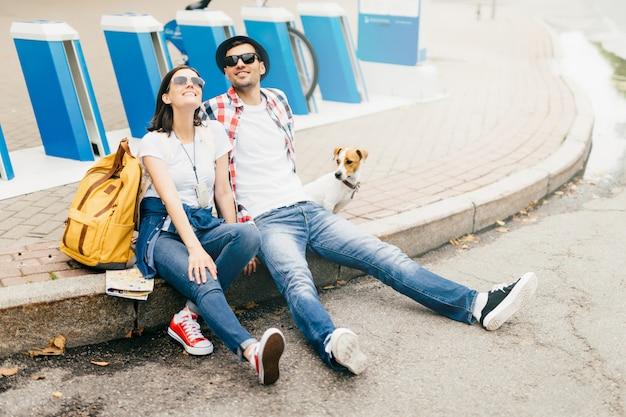 穏やかな若い男性と女性の旅行者と彼らのペットが舗装の上に座って、天気の良い日を楽しんでいる間、陽気な表情を持ち、公園で長い散歩の後疲れている。旅行のコンセプト