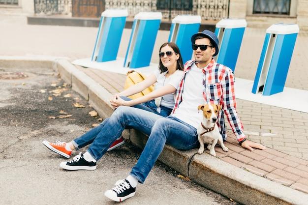 ファッショナブルな男性と女性の横向きの肖像、サングラスをかけ、屋外の舗装の上に座って、遠くを見て、どこへ行くかを考えて、一緒にリラックスします。レジャー、ライフスタイルコンセプト