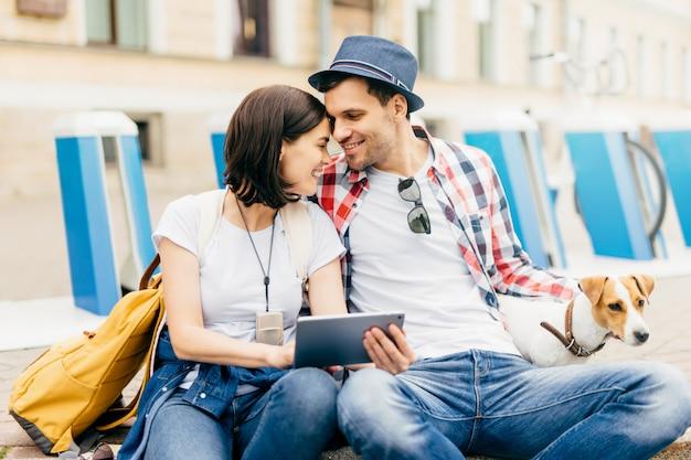 屋外で座って、タブレットでオンラインで映画を見て、休息をとり、心地よく笑っている間、愛の若いカップルは、良い関係を持ち、お互いを大きな愛で見ています。人、関係