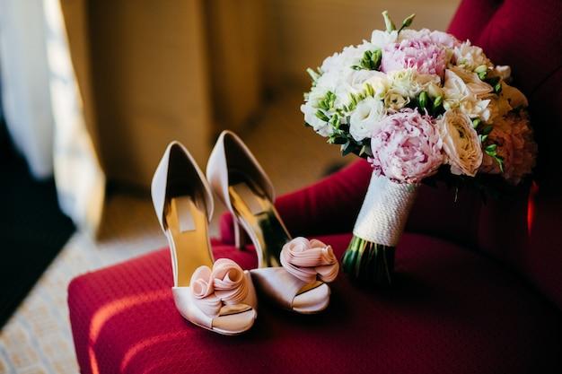 Свадебная обувь и свадебный букет с нежными цветами на красном стуле