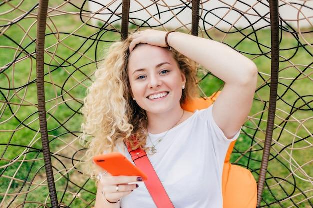 Улыбчивая европейка с широкой улыбкой, вьющимися волосами, одетая в повседневную белую футболку, использует современное электронное устройство для серфинга в социальных сетях