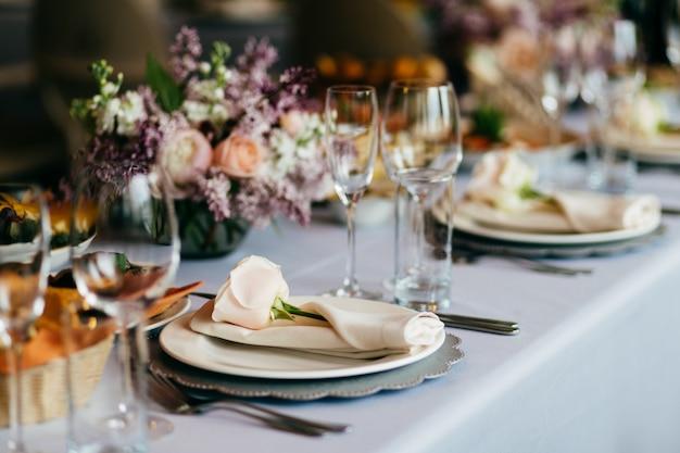 Пустая тарелка, бокалы, вилки, салфетка и цветы на столе, накрытом белой скатертью