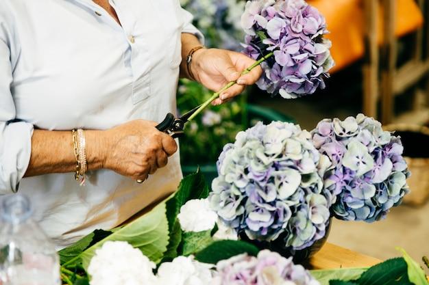 Женщина флорист делает красивые букеты стоя в цветочном магазине