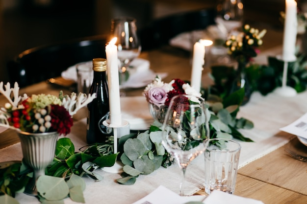 キャンドル、装飾、カトラリー、お祝いテーブルのドリンク。花とキャンドルで飾られた結婚式のテーブル。