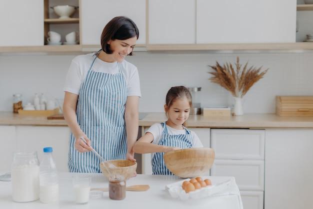 ブルネットの母親と小さな子供はクッキー生地を作る