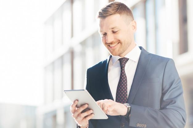ハンサムな繁栄した実業家は、タッチパッドを介してインターネットで有用な情報を読み取ります