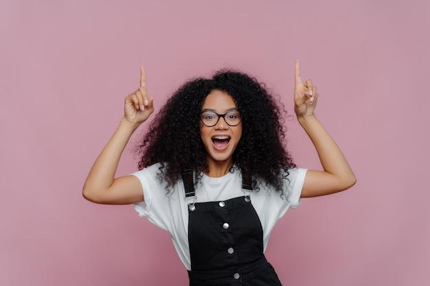 幸せなアフロアメリカンの女性は、両方の人差し指を上に指します