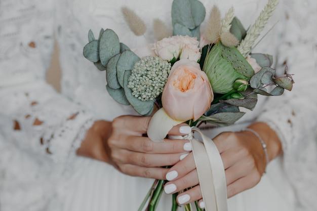 花嫁の手の中の美しい花。結婚式の準備の白いウェディングドレスの女性。