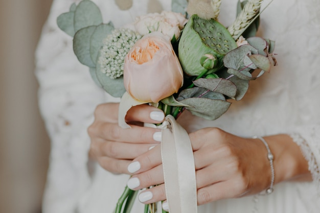 素敵な花束を持つ美しい花嫁は結婚式の準備をします。花嫁の手は屋内の花を保持します。