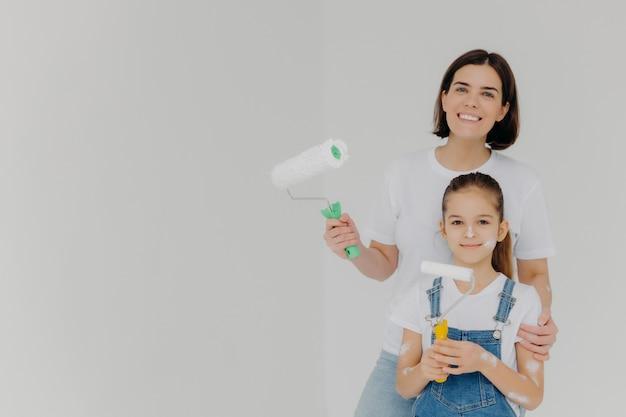 Улыбающаяся заботливая мама обнимает дочь, стоит с малярными валиками