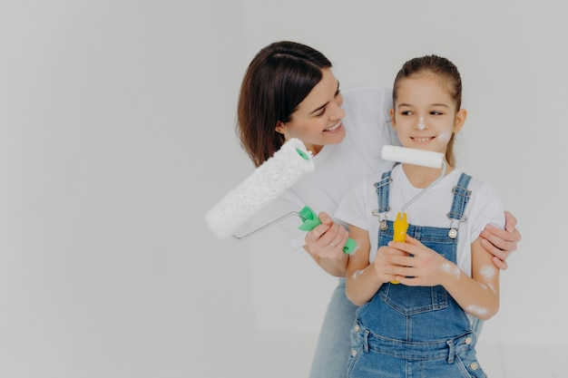 思いやりのある母は小さな娘を愛で抱きしめ、一緒に新しい家の壁を塗る