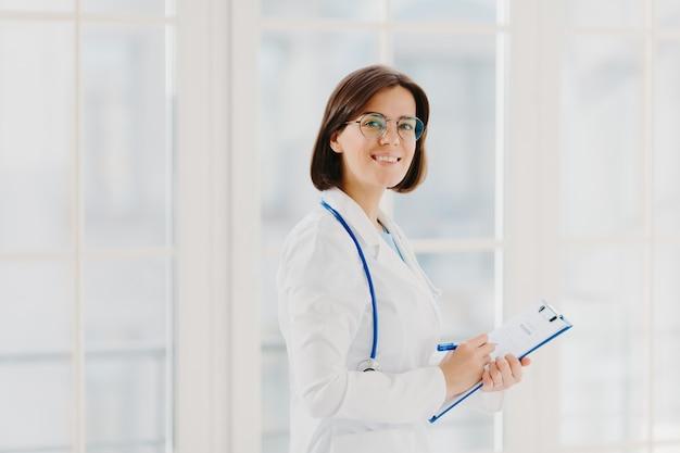 女医の水平ショットは、クリップボードで医療フォームを埋め、屋内に立って、丸眼鏡、白いガウン、聴診器を着ています