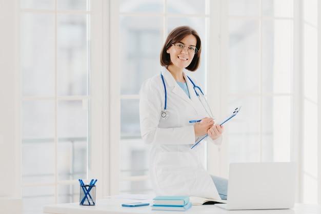 熟練した女性セラピストまたは心臓専門医がクリップボードに情報を書き込み、患者に相談して治療する準備ができている