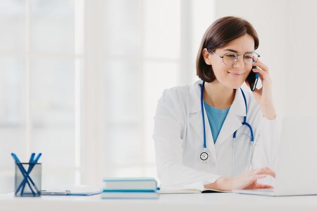 Улыбающийся терапевт сосредоточен на экране ноутбука, звонки через современный смартфон