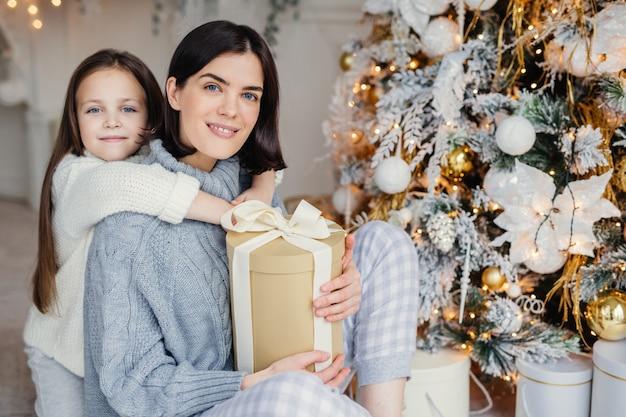 ありがたい小さな女性の子供は、プレゼントをくれた母親を抱きしめ、一緒に素晴らしい忘れられない時間を過ごし、クリスマスを祝います。ブルネットの女性と娘はモミの木の下でプレゼントを探す
