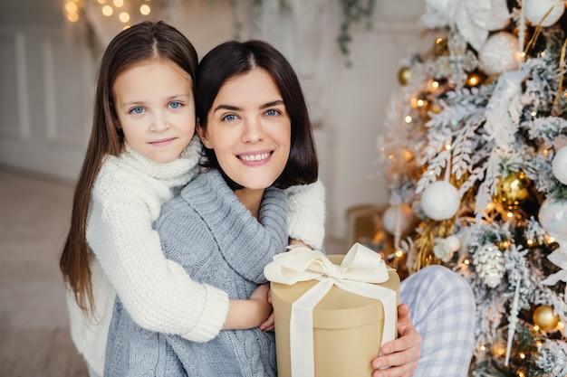 Очаровательная голубоглазая маленькая малышка с большой любовью обнимает свою маму, которая держит упакованную подарочную коробку, стоит возле украшенной елки, с радостью отмечает зимние каникулы. люди, праздник, концепция подарков