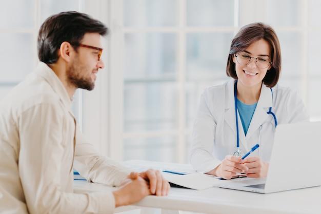Врач и пациент что-то обсуждают, говорят о диагностике, используют портативный компьютер