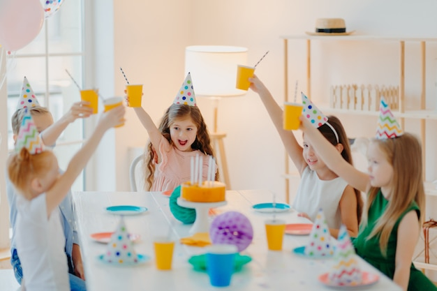 陽気な就学前の子供たちのグループが一緒に誕生日を祝って、楽しんで、飲み物のカップで応援、お祝いの帽子をかぶって、おいしいケーキを食べます
