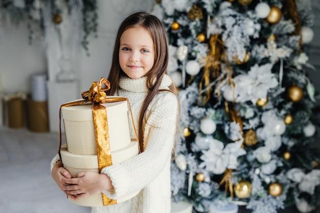 愛らしいかわいいかわいい小さな女性の子供の屋内ショットは暖かいニットの服を着て、巨大な包まれたプレゼントを保持し、サンタクロースから受け取る、装飾された美しい新年の木の近くに立つ